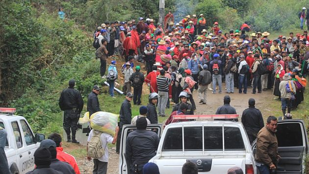 A group of around 100 community members are gathered together to block a dirt road.