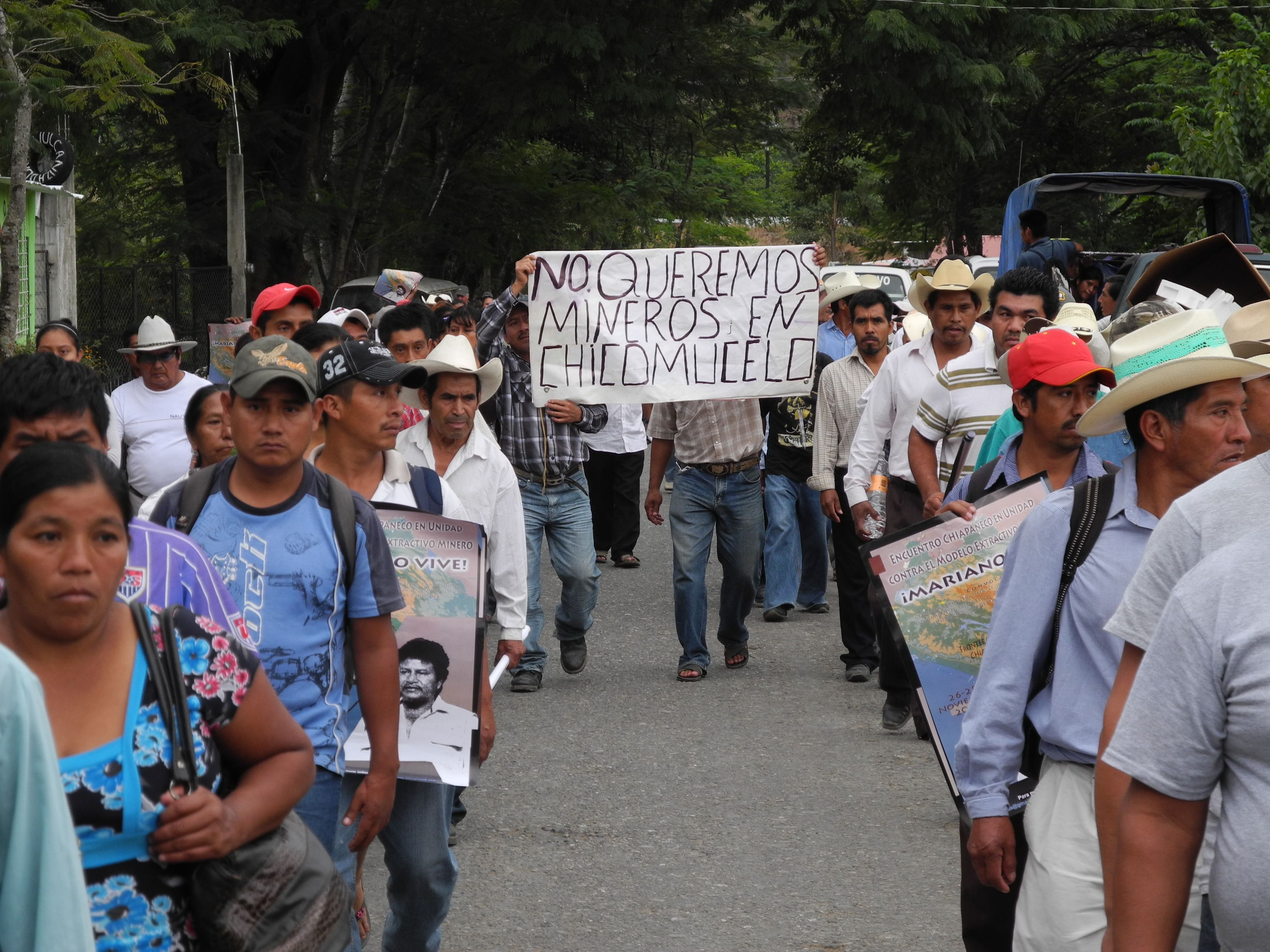 """A large crowd of people moves down a tree-lined street towards the camera. A banner in the center of the crowd reads """"We do not want miners in Chicumucelo"""""""