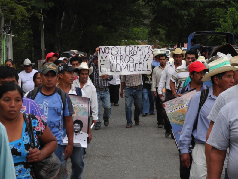 "A large crowd of people moves down a tree-lined street towards the camera. A banner in the center of the crowd reads ""We do not want miners in Chicumucelo"""