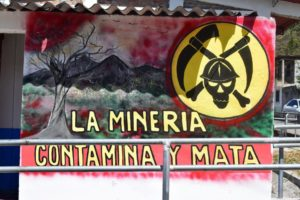 A sign with a skull and mining tools for the crossbones reads Mining Pollutes and Mining Kills