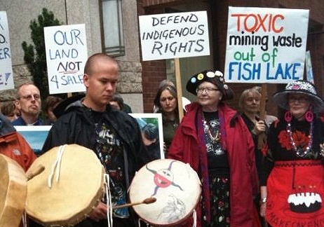 A group of Indigenous protesters with signs and traditional drums