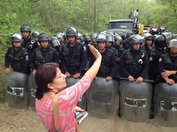 woman stands with her hand held up stands in front of a line of Guatemalan National Police in riot gear