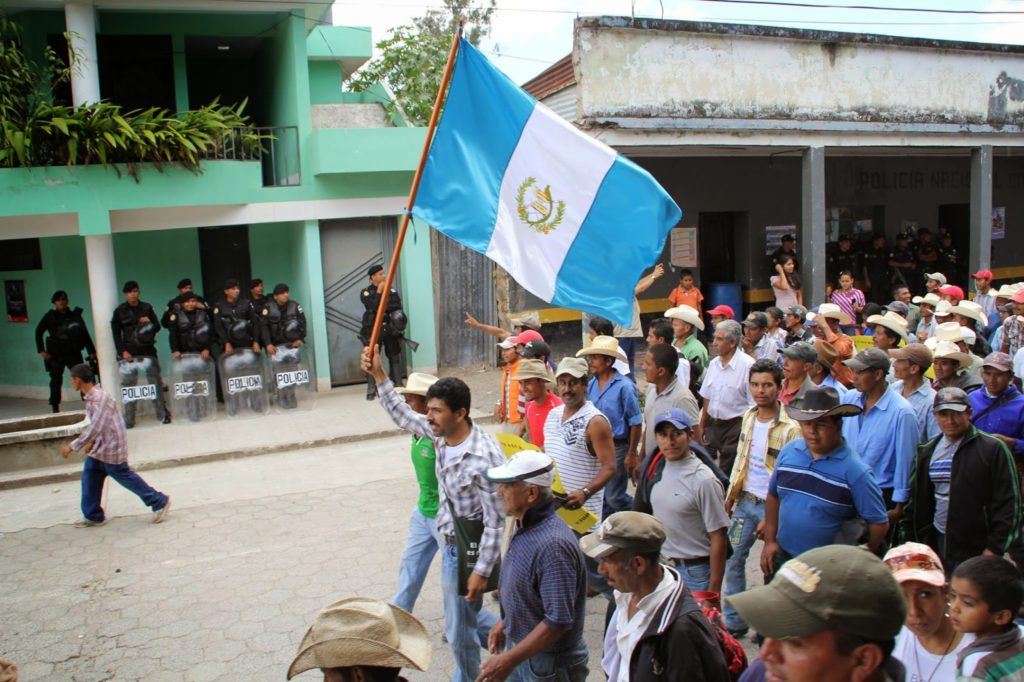 A crowd of people march from the left. Someone leading the march hold a Guatemalan flag.