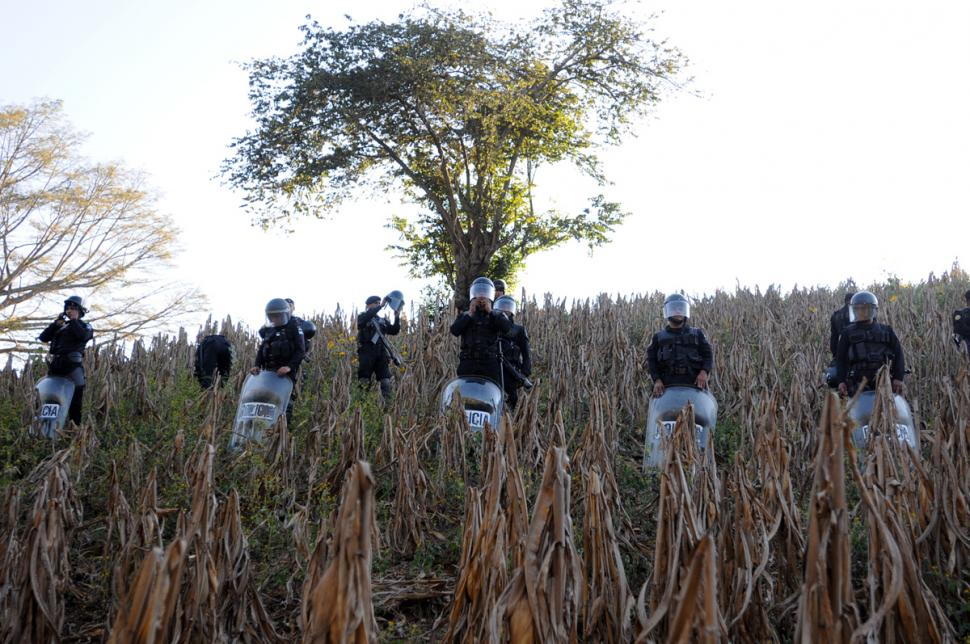 Police in riot gear line up in a field.