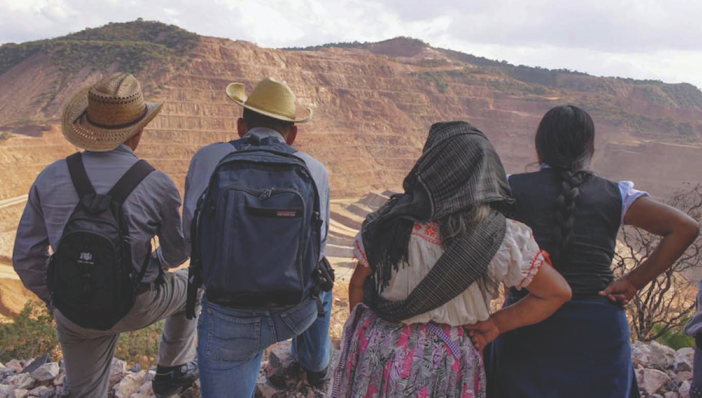 two men and two women from behind overlooking an open pit mine