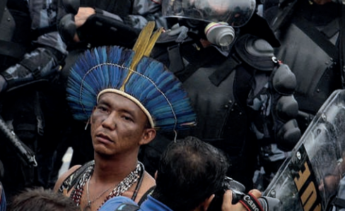 indigenous person of unknown origin wearing blue headress surrounded by riot police