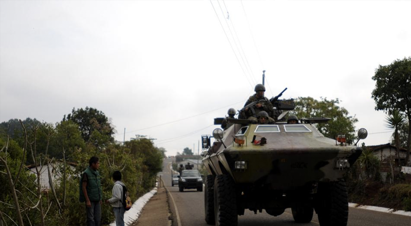 a tank carrying soldiers with guns driving down a paved road
