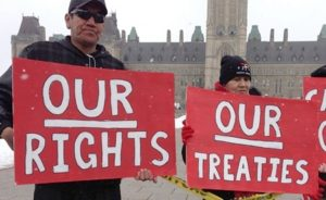 two Indigenous people stand in front of Parliament with red signs that reas Our Rights, Our Treaties