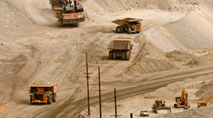 Several dump-trucks drive around an open pit mine