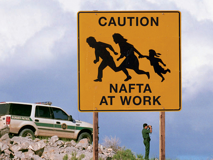 """A US Border Patrol agent looks through binoculars for undocumented migrants. In the foreground a yellow sign with an outline of a family fleeing is captioned 'Caution NAFTA At Work."""""""