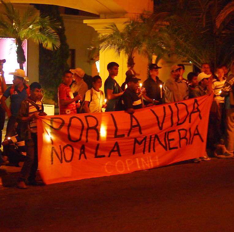 At night, a group of people holding candles gather behind a red banner with black lettering that reads 'POR LA VIDA. NO A LA MINERIA.'
