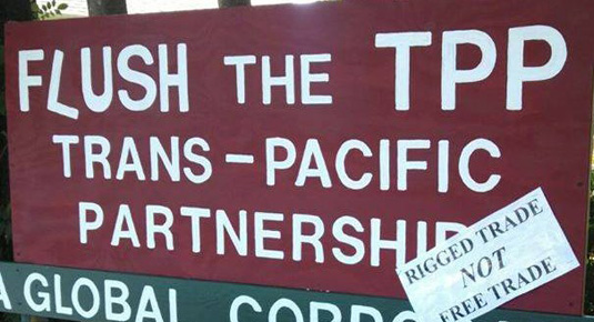 A maroon and green banner reads 'Flush the TPP Trans-Pacific Partnership: Rigged Trade NOT Free Trade'