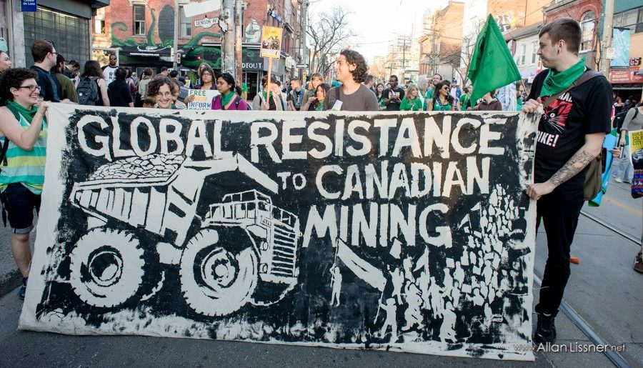 "A crowd of people behind a banner that reads ""Global Resistance to Canadian Mining"" showing an image of a crowd of protestors standing in the path of a huge dump truck"