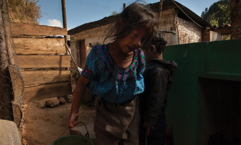 A young Indigenous Maya-Mam girl carries a bucket of water