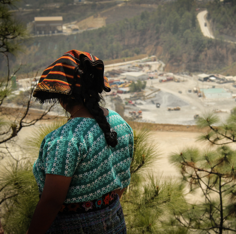 Seen from behind, an Indigenous woman in a turquoise patterned top gazes down towards an open pit mine.