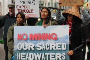 "A group of Indigenous protesters gather behind a sign that reads ""No mining our sacred headwaters"""