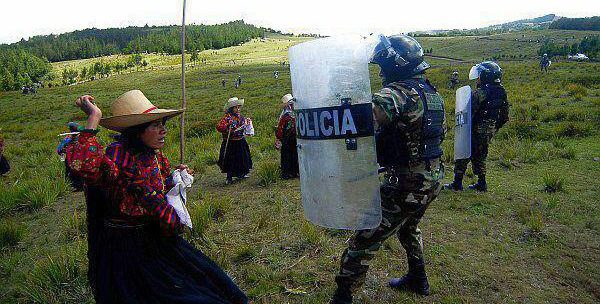 An Indigenous woman in traditional dress faces off against a police officer in riot gear. The backdrop is rolling green hills.